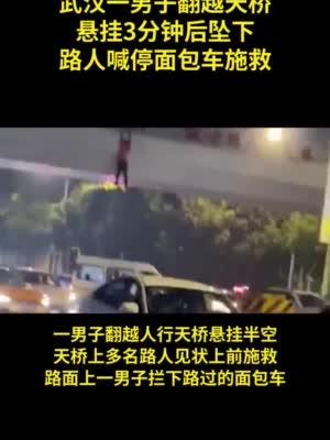 武汉一男子翻越天桥悬挂后坠下,路人喊停面包车接住